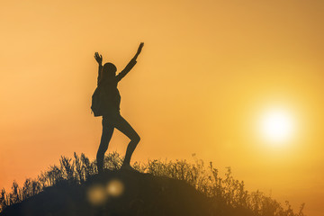 silhouette of a young happy girl with a backpack holding her hands up the sportswoman, on top of the mountain in the glare of the sun in the sunset. Fitness, victory