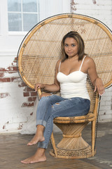 Beautiful and sexy young biracial woman wearing a white tank top and blue jeans sits in a large wicker chair