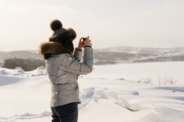 woman in winter suit photographing snow-covered field