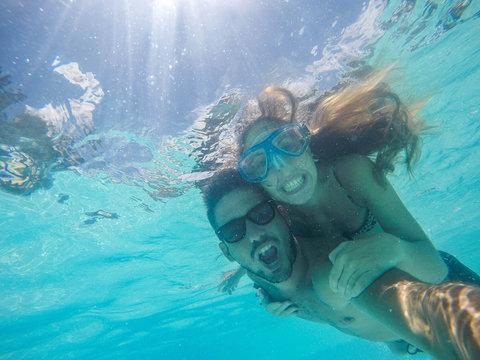 Couple in love taking a selfie doing snorkeling in the ocean