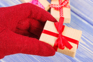 Hand of woman in gloves with gifts for Valentines Day
