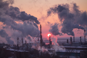 the chimneys of a refinery with smoke and steam with the pinkk sunset on the background