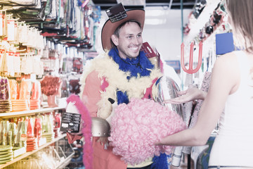 Smiling man with girlfriend trying on cowboy hat