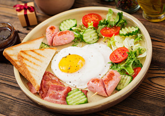 Breakfast on Valentine's Day - fried egg in the shape of a heart, toasts, sausage, bacon and fresh vegetables. English breakfast