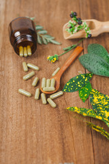 Herbal medicine capsules spilling out of a bottle ,soft focus.