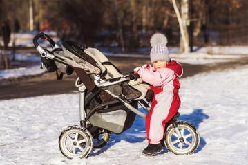 little child is sitting in a stroller in winter
