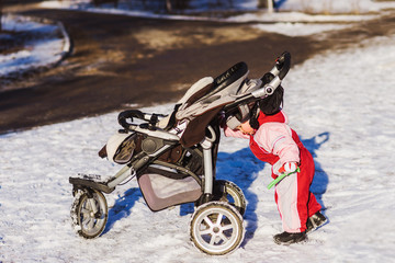 little baby pushes his stroller in winter