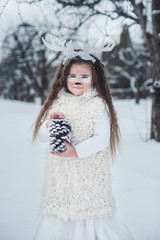fairy tale girl. Portrait a little girl in a deer dress with a painted face in the winter forest