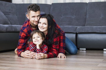 Happy beautiful family dad, mother and daughter smiling together at home lying on the wooden floor in the living room