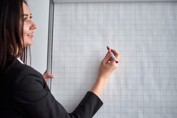close up of woman with marker writing or drawing something on flip chart