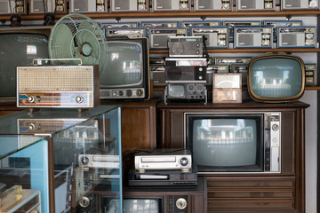 Old vintage different radios, television and electronic in antique store shelves.