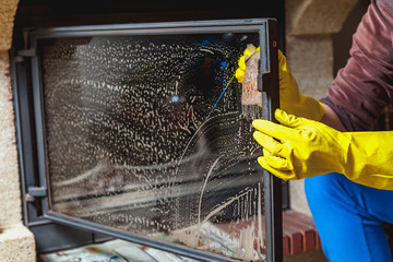 Hands in yellow gloves wash glass fireplace door