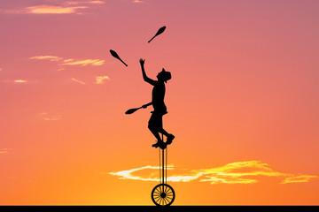 juggler with ninepins at sunset