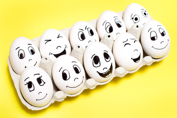Eggs with drawn cartoon faces with various emotions in box