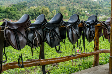 Saddle on wooden fence
