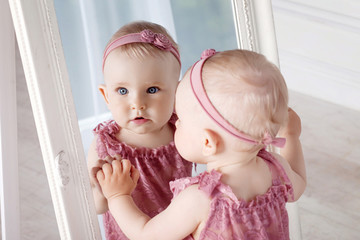 Little pretty girl plays with a big mirror. Portrait of the little girl with reflection in a mirror