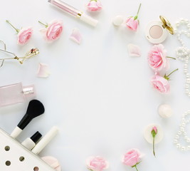 Flat lay, top view feminine desk, female make up accessories and bouquet roses.Beauty blog , Holiday concept.Copy space