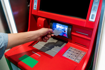 Hand of Asian woman inserting ATM card into ATM machine.