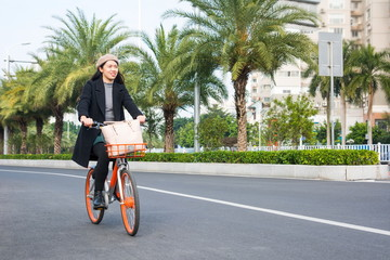 Asian office lady riding bicycle through urban area