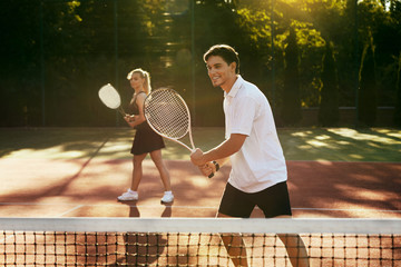 Man And Woman Playing Tennis On Court.
