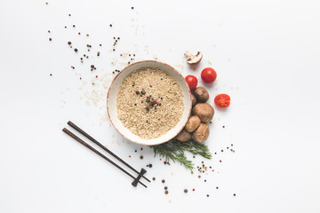 flat lay composition of raw rice in bowl with mushrooms and tomatoes on white surface with chopsticks