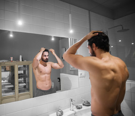 Attractive muscular bearded man preparing his hair in front of mirror in the bathroom.