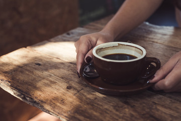 Closeup image of woman's hands holding and giving a cup of hot coffee on wooden vintage table
