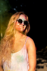 Beautiful blonde model in sunglasses, covered with colorful powder Holi