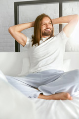 Happy Man Sitting On Bed In Morning After Waking Up
