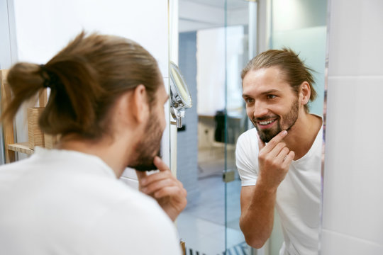 Man Looking In Mirror In Bathroom.