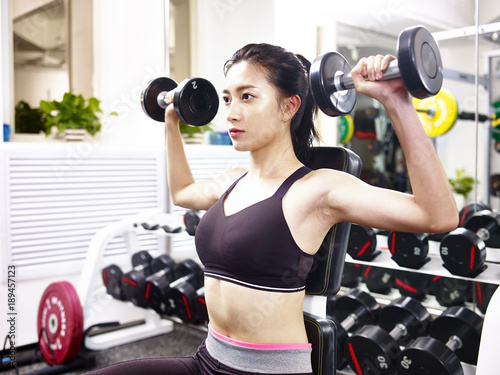 young asian woman exercising working out in gym fotolia com の