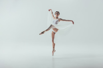young elegant ballerina dancing in studio, isolated on white