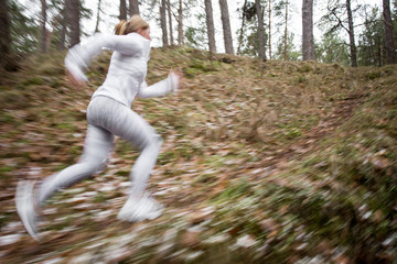 Motion blurred photo of woman running in woods in cold weather