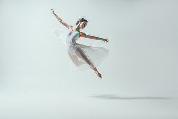 elegant ballet dancer in white dress jumping in studio, isolated on white