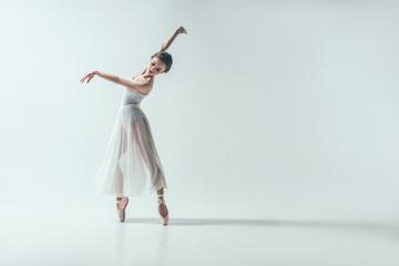 elegant ballerina dancing in studio, isolated on white