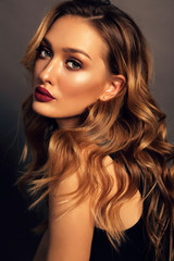 beautiful girl with blond curly hair and evening makeup