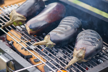 Aubergine on barbecue grill on hot charcoal and fire. Preparing healthy food on holiday. Cooking vegetables on flames. Delicious meal for vegetarians and vegans