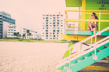 Beautiful woman in bikini at the lifeguard station, Miami, USA