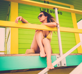 Beautiful woman in bikini at the lifeguard station, Miami, USA