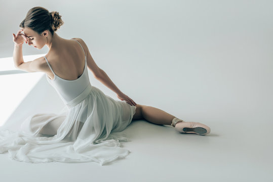 back view of elegant ballerina sitting in white dress and ballet shoes