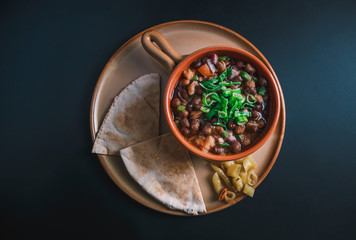 A high angle view/color studio image of Egyptian, Arabian, Middle Eastern Traditional food (Fava Beans with Vegetables/Green Paprika) A.K.A (Foul) Also served in Lebanon and most of Arabian countries.