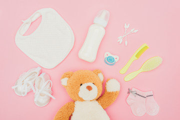 top view of teddy bear and baby equipment isolated on pink