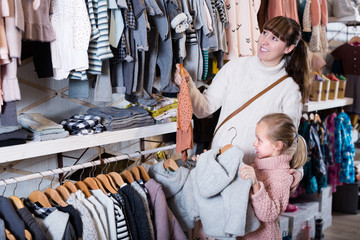Pregnant mother and daughter choosing clothes for baby