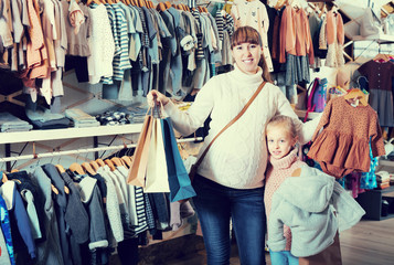 Mother and girl boasting purchases in cloths shop
