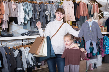 Smiling pregnant woman and girl enjoying purchases