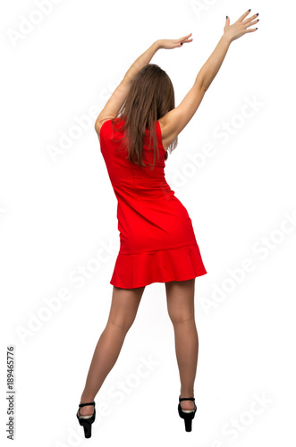 Sexy girl in red dress in stockings and in high heels shoes is standing  with rised up hands and is dancing isolated on white background. Back view. 5cebc223868