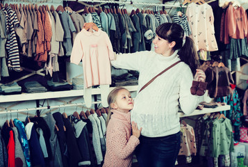 Pregnant mother and daughter purchasing clothes