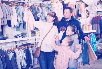 Family choosing baby clothes