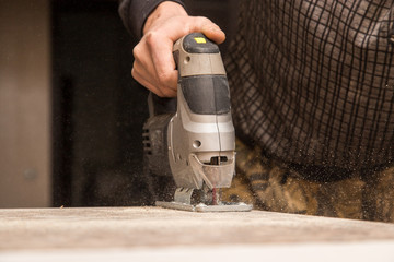 Master cuts wood with a jig saw