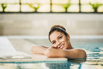 Young beautiful woman enjoying summer holiday in swimming pool at resort hotel. Spa, retreat, relaxation concept. Beauty, health and body care. Healthy living